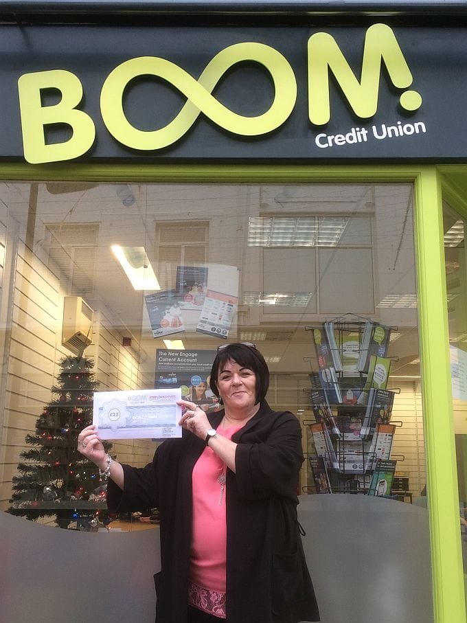 Jenny Attree (BOOM! Credit Union Volunteer) holding a £25 Stop Loan Sharks voucher