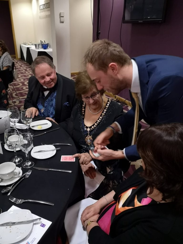 Mayor of Worthing, Cllr Hazel Thorpe, watches a card trick by magician, Harvey Woods