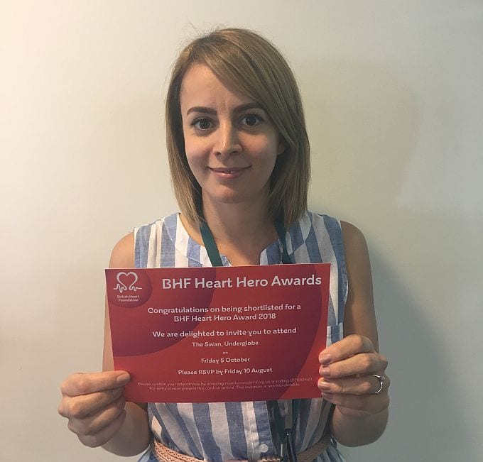 Michaela Wheatley holding her invitation to the British Heart Foundation Heart Hero Awards