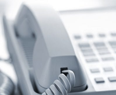 Desktop telephone closeup hung up with cord
