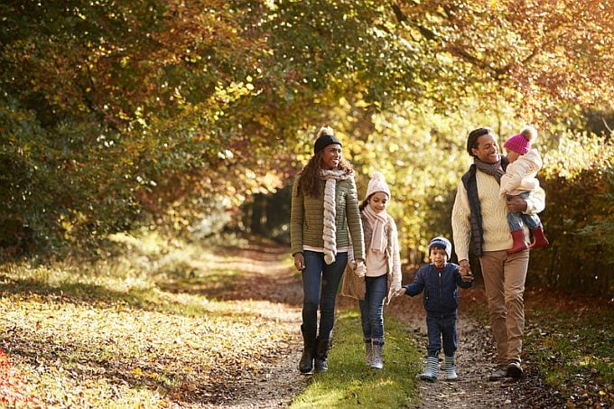 Front View Of Family Enjoying Autumn Walk In Countryside