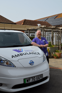 Healthcare Assistant at Care for Veterans, Lee Brace, with the electric ambulance and solar panels in the background.