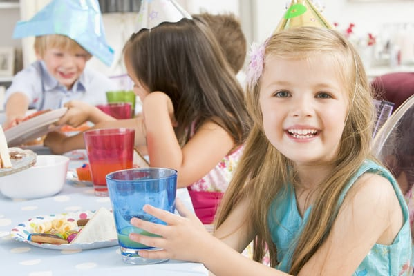 Young girl at childrens party sitting at table with food smiling